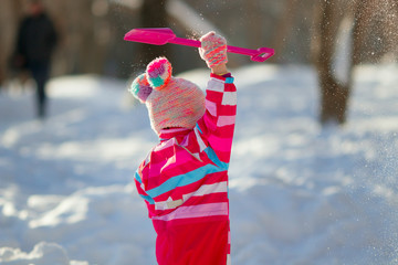 Cute toddler girl wearing bright colored overall playing with snow and shovel in a sunny cold winter day