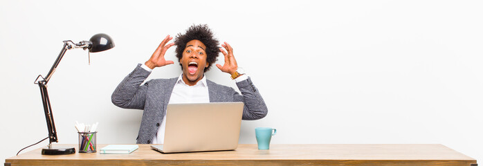 young black businessman screaming with hands up in the air, feeling furious, frustrated, stressed and upset on a desk