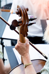 Cropped image of a back turned woman playing cello