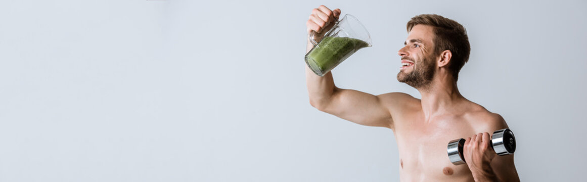 panoramic shot of smiling shirtless sportsman holding smoothie and dumbbell isolated on grey