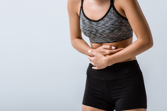 partial view of sportswoman with stomach pain isolated on grey