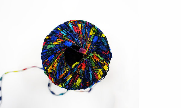 Isolated Spool of Multi-Colored Thread Unraveling Against a White Background
