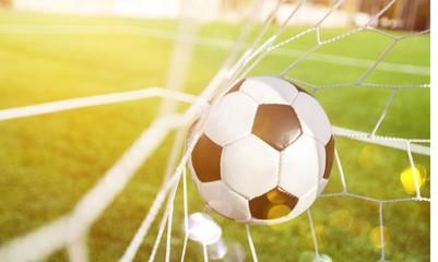 Soccer ball in goal on background