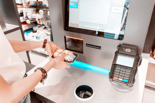 The girl in the supermarket buys sushi and makes a purchase at the checkout self-service