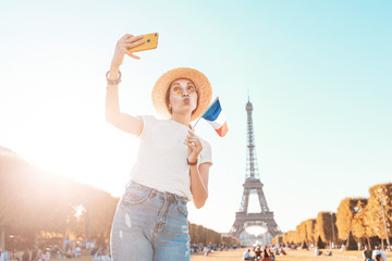 Happy Asian girl taking selfie photo on her smartphone on the background of the Eiffel tower. Travel and image quality concept