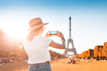 Happy Asian girl takes photo on her smartphone on the background of the Eiffel tower. Travel and image quality concept