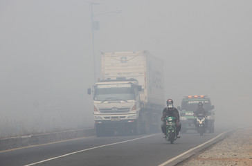 Motorists ride motorbikes through the haze due to the forest fires in Banjarbaru