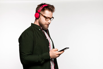 Portrait of bearded man listening to music with headphones. Stylish model wearing fashionable jacket and light shirt. Copy space on right side. Beauty and fashion concept. Isolated on white background Wall mural