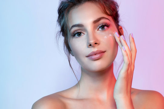 Cute woman with natural make-up applying moisturizing facial cream. Portrait of wonderful female looking at camera with calmness. Beauty and skincare concept