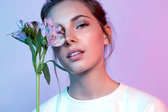 Beautiful woman in white t-shirt covering face with wonderful blossom in neon light. Portrait of lovely female looking at camera with tenderness. Beauty and fashion concept