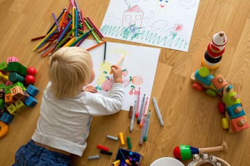 Little blonde toddler boy, drawing with pastels and coloring pens, playing with wooden toys