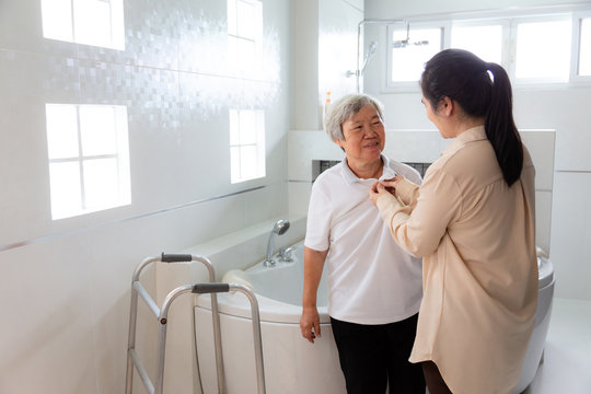 Asian daughter or female caregiver taking off the clothes of senior mother before taking a shower in bathroom,take care closely,concerned about the safety of elderly woman, accidents in the bathroom