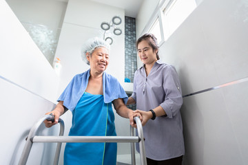 Asian daughter or female care assistant service,help,support senior woman taking shower in bathroom,happy mother walking with walker in bathroom,safety of elderly people, family relationship concept