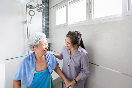 Asian daughter or female care assistant service,help,support senior woman taking a shower in bathroom,take care closely,happy mother is difficult to help herself, the safety and accidents of elderly
