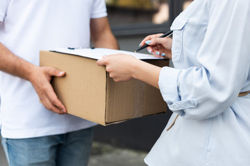 cropped view of delivery man holding box near woman signing paper on clipboard outside