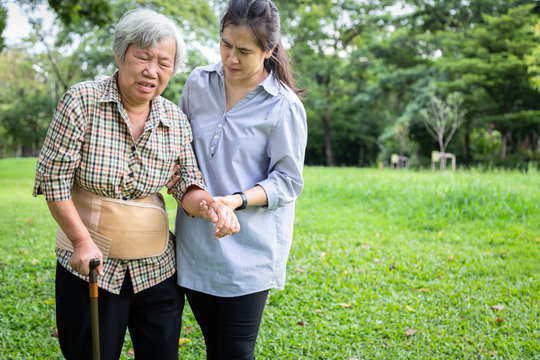 Asian senior mother backache use back support belt for protect her back pain,muscle injury,middle-aged daughter or care assistant help,support elderly woman feel sudden back pain while walking at park