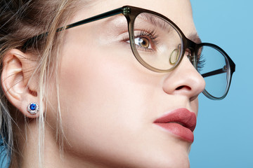 Close-up portrait of attractive young woman in glasses on blue background