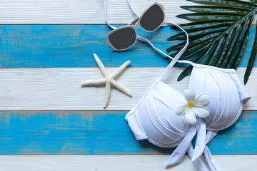 Summer items fashion woman swimsuit Bikini, starfish and sunblock. Travel and vacations in the holiday, wood white background, top view. Summer Concept.