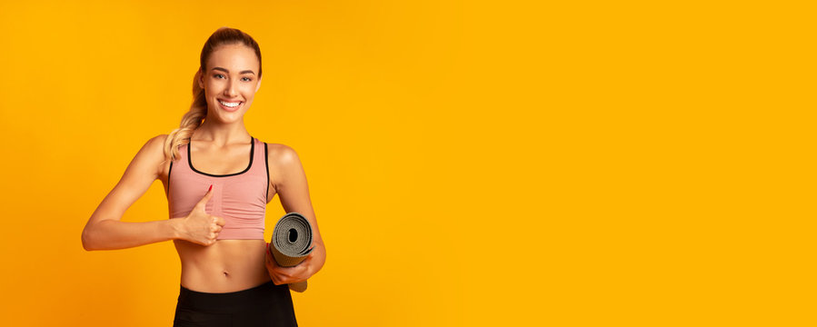 Girl Holding Rolling Mat Gesturing Thumbs-Up On Yellow Background, Panorama