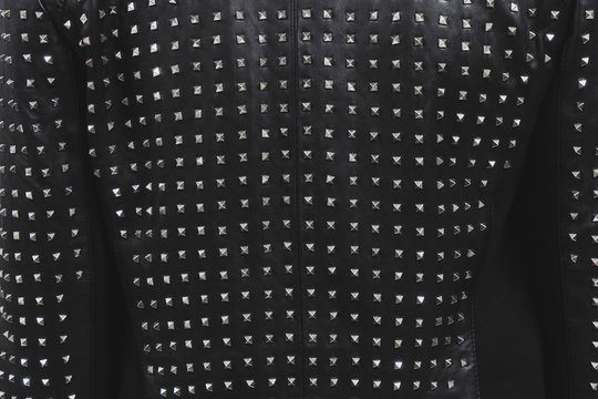 Back of a black leather jacket with metal rivets. Biker or punk studded style. Sample of stylish clothing products. Textured background. Fashionable rocker clothes. Horizontal photo.