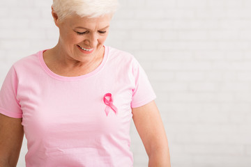 Elderly Woman Looking At Pink Cancer Ribbon On T-Shirt, Indoor