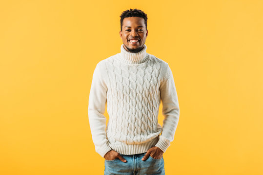 African American man in knitted sweater holding hands in pockets, smiling and looking at camera isolated on yellow