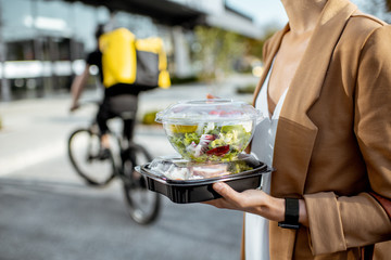 Photo sur Aluminium Magasin alimentation Businesswoman holding lunchboxes with fresh takaway food outdoors. Male courier on a bicycle on the background. Takeaway restaurant food delivery concept