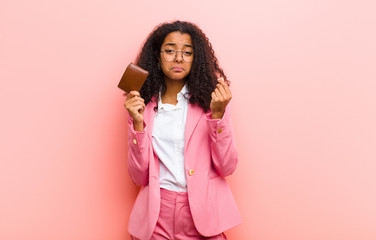 young black pretty business woman with a wallet against pink wall background