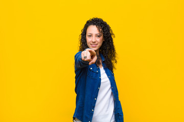 young pretty woman pointing at camera with a satisfied, confident, friendly smile, choosing you against orange wall