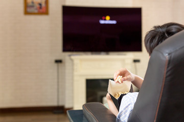 People hand with popcorn watching television at home.