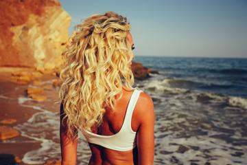 Blonde curly hair tan girl watching ocean