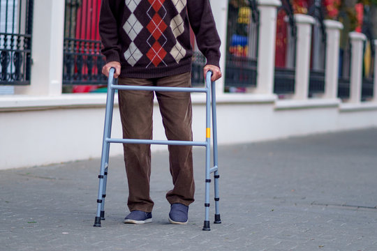 An elderly person uses a walker to walk around the city. Orthopedic support during leg injuries and help for disabled people