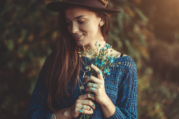 Happy attractive autumn brunette boho chic woman in a brown hat and knitted blue sweater with bouquet of wildflowers in hands in autumn forest outdoors in fall. Boho fashion