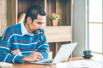 Arab businessman in casual clothes  working in the office with laptop, paper, note and a cup of coffee on working table.