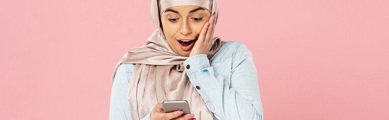 shocked muslim girl in hijab using smartphone isolated on pink