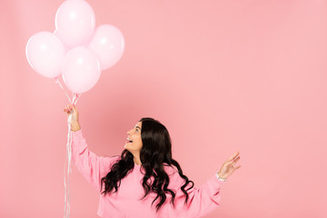 beautiful excited girl holding pink balloons, isolated on pink