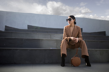 Fashion portrait of a successful business woman sitting on stairs. City background