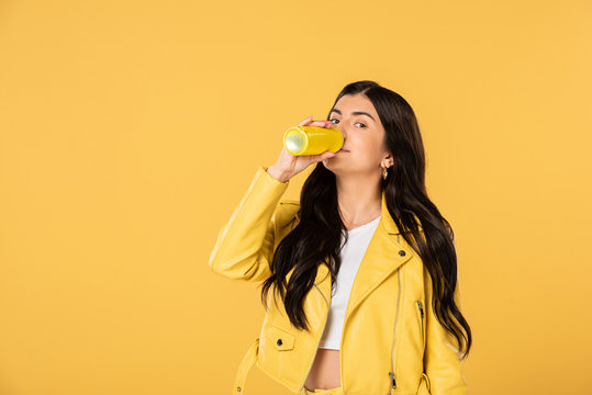 attractive woman drinking soda from can, isolated on yellow