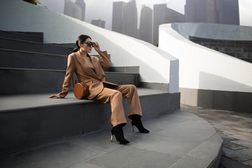 Portrait of a successful business woman sitting on stairs. City background