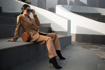 Portrait of a successful business woman sitting on stairs. City background Wall mural