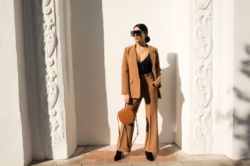Fashion portrait of a successful business woman standing on against a white wall. Business suit and bag in her hands.