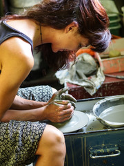 Young girl working on pottery at her home electrical  rotating pottery wheel