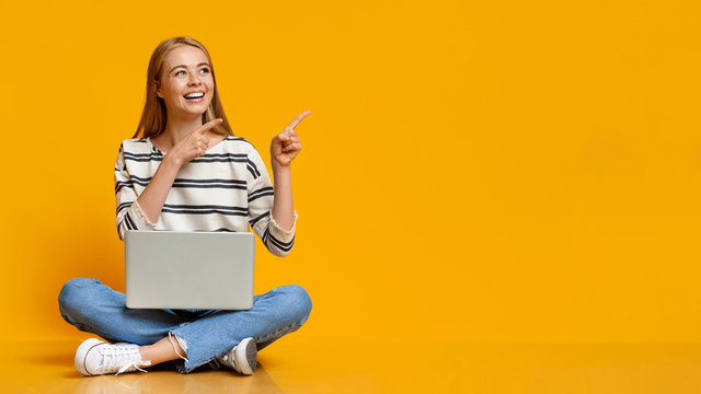 Cheerful teenage girl sitting with laptop, pointing at yellow background