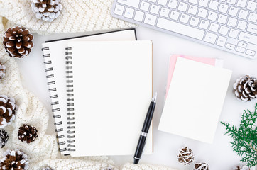 Christmas white workplace with blank opened spiral notebooks, pen and keyboard arrangement with pine cones and fir branches. Top view mockup