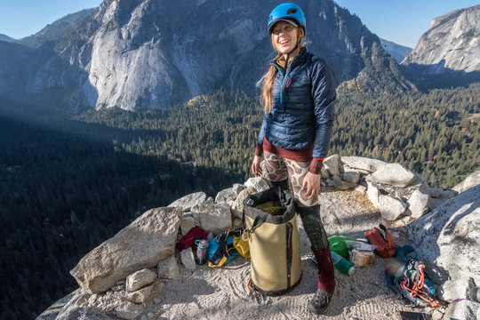 A young woman climber smiles as she stands on last night's bivy ledge