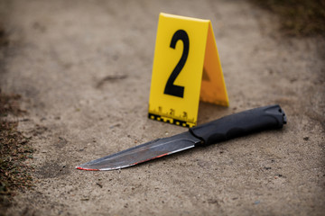 Crime scene investigation, bloody knife with crime markers on the ground, evidence of murder