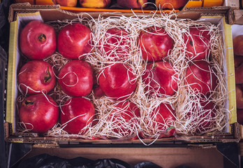Box of pomegranates protected from shocks by wood wool