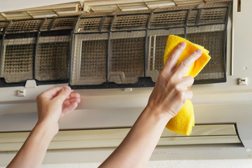 Closeup woman hand cleaning air conditioner