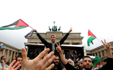People flash V-signs and wave Palestinian flags as they gather in front of the Brandenburg Gate in Berlin