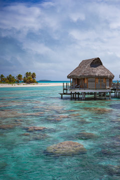 Vertical of overwater bungalow luxury resort in calm tropical lagoon paradise